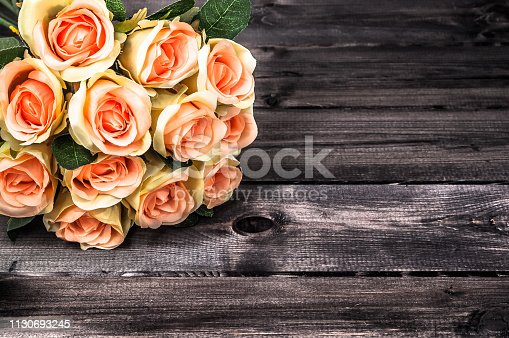 680461500istockphoto Bouquet of roses on wooden background. Mothers day card. 1130693245