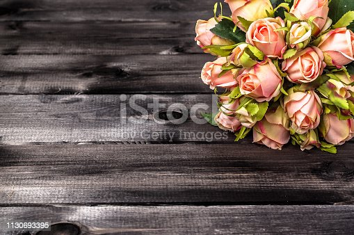 680461500istockphoto Bouquet of roses on wooden background. Mothers day card. 1130693395