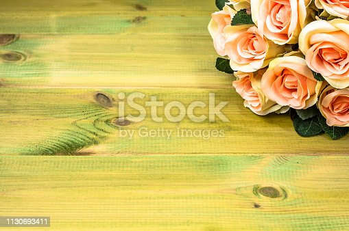 680461500istockphoto Bouquet of roses on wooden background. Mothers day card. 1130693411