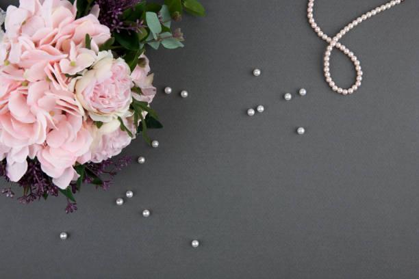rosenstrauß mit perlenkette auf grauem hintergrund - verlobungsfeier einladungen stock-fotos und bilder