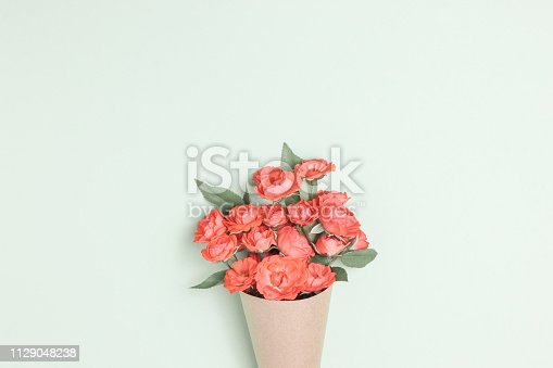 Bouquet of small red roses in vintage paper on the table. Top view, flat lay, overhead. Invitation card. mothers day background. Floral invite card
