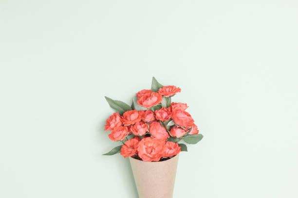 boeket van kleine rode rozen in vintage papier op tafel. - boeket stockfoto's en -beelden
