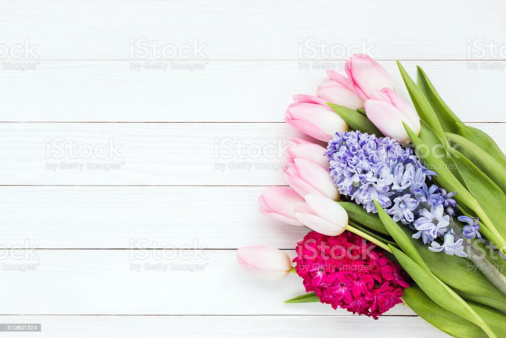 Bouquet of spring flowers on white wooden background. Top view stock photo