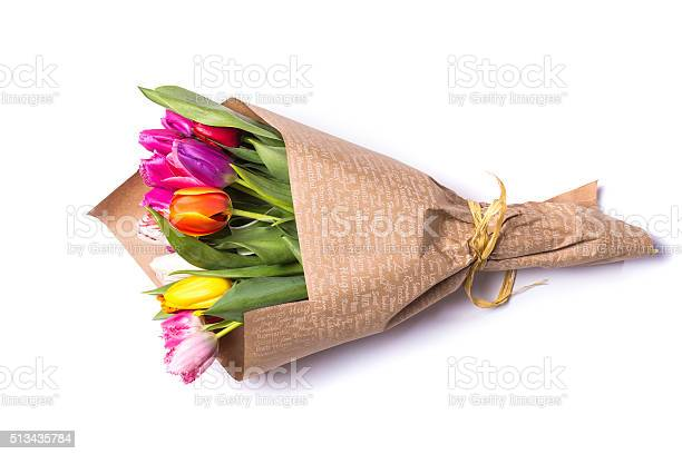 Bouquet of spring tulips flowers wrapped in paper  isolated on white backgroundBouquet of spring multicolor tulips flowers wrapped in present paper  isolated on white background