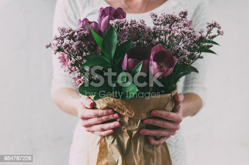 istock Bouquet of spring tulips flowers wrapped in gift paper 654767226