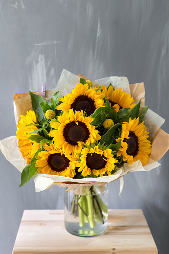 Bouquet of sunflowers and wild flowers on wooden table.