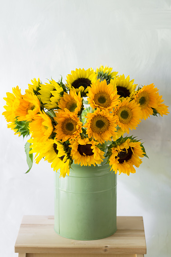 Bouquet of sunflowers and wild flowers on wooden table, copy space. green cans