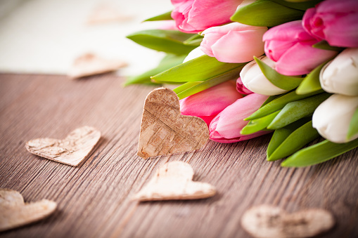 bouquet of tulips and a heart on wooden table