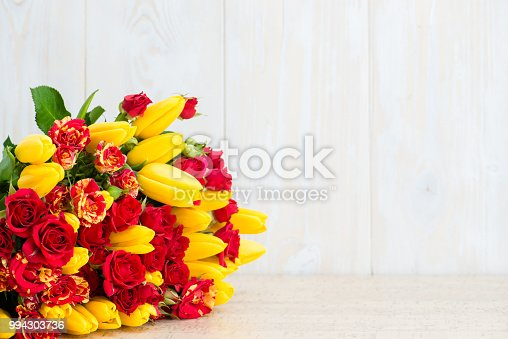 Bouquet of tulips and bush roses on a wooden background. Copyspace