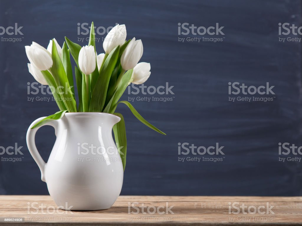 Bouquet of tulips in a oldfashioned rustic vase pot on a wooden table. Light colour flowers in white jug on a blur background. stock photo