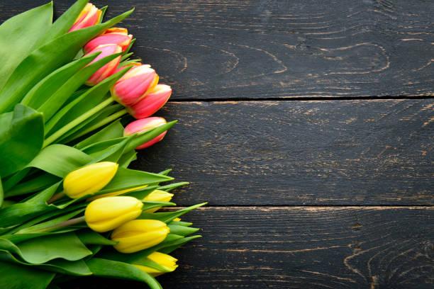 strauß tulpen auf rustikalen holz dunkel - holzblumen stock-fotos und bilder