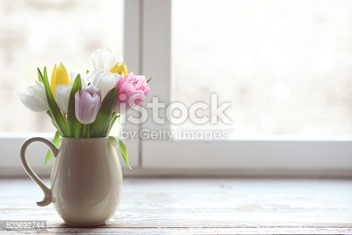 bouquet of tulips in a vase on a window sill at the window