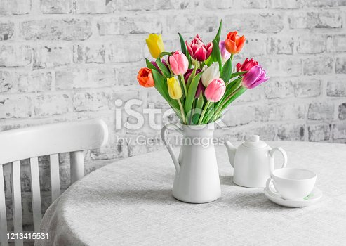 697868238 istock photo Bouquet of tulips , teapot and teacup on the table in the bright kitchen. Cozy home concept 1213415531