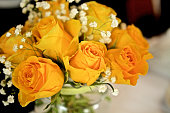 Glass Vase with vibrant coloured yellow roses, baby's breath