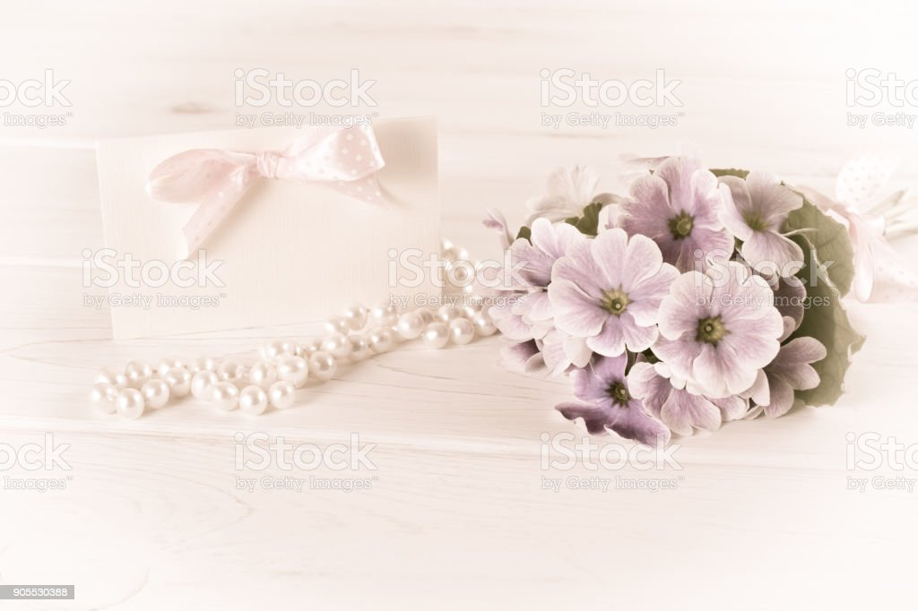 Bouquet of violet primroses with greeting card and pearl necklace stock photo