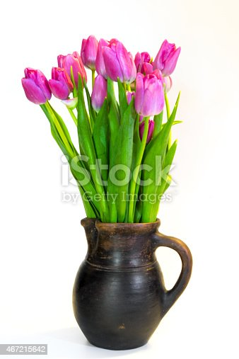 istock Bouquet of violet tulips in an old clay pot 467215642