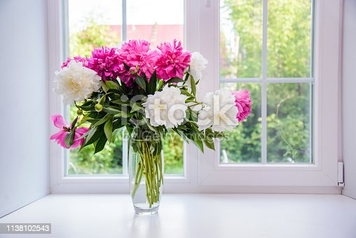 Beautiful bouquet of white and pink peonies in a vase on the windowsill