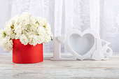 istock Bouquet of white roses in a red box and a white photo frame close-up. 1199000441