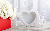 istock Bouquet of white roses in a red box and a white photo frame close-up. 1199000716