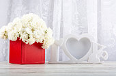 istock Bouquet of white roses in a red box and a white photo frame close-up. 1199000727