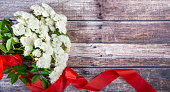 istock A bouquet of white roses with a red ribbon on a background of dark boards. 1196466957
