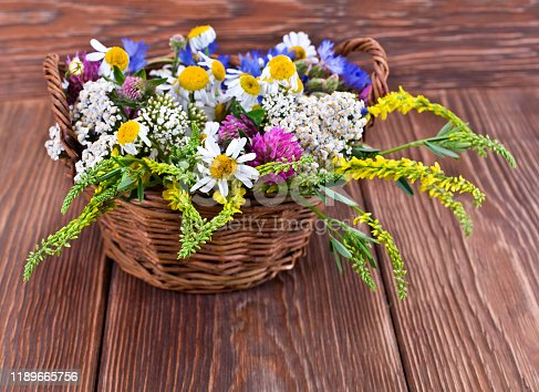 Bouquet of wild flowers in a basket on a wooden background.
