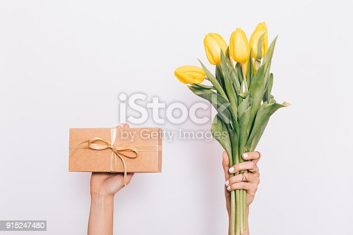 istock Bouquet of yellow tulips and a gift box with a bow 915247480