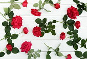 istock Bouquet pattern of beautiful red roses on white wooden background.Top view.Copy space 1041959234