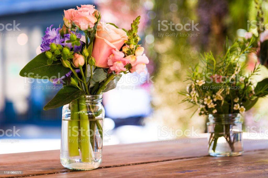 Close up color image depicting bouquets of fresh flowers displayed in...