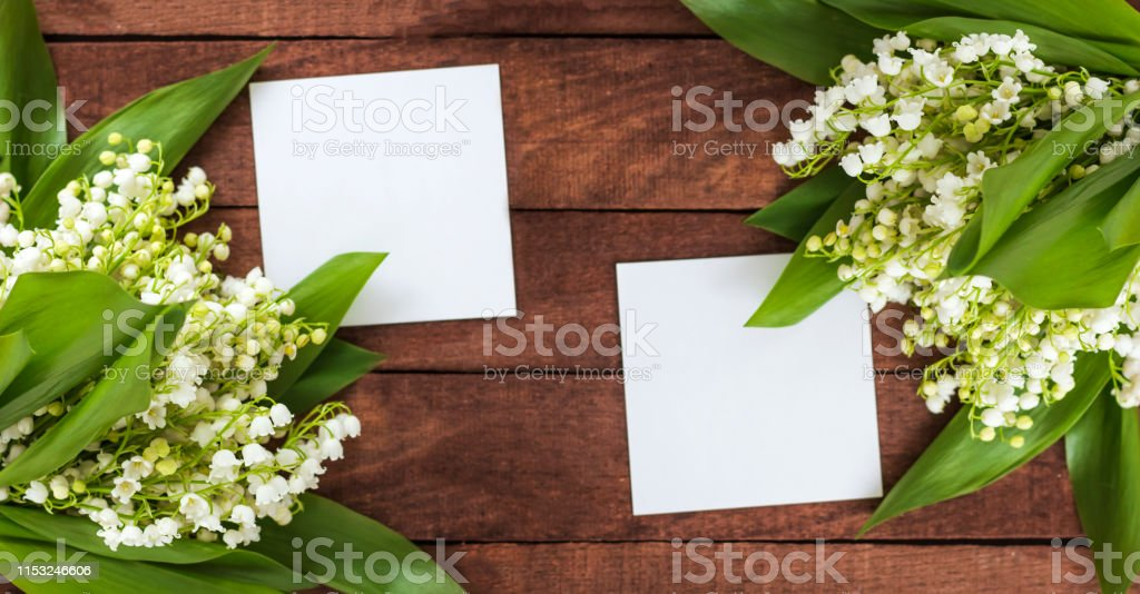 bouquets of lilies of the valley with space for text from white...