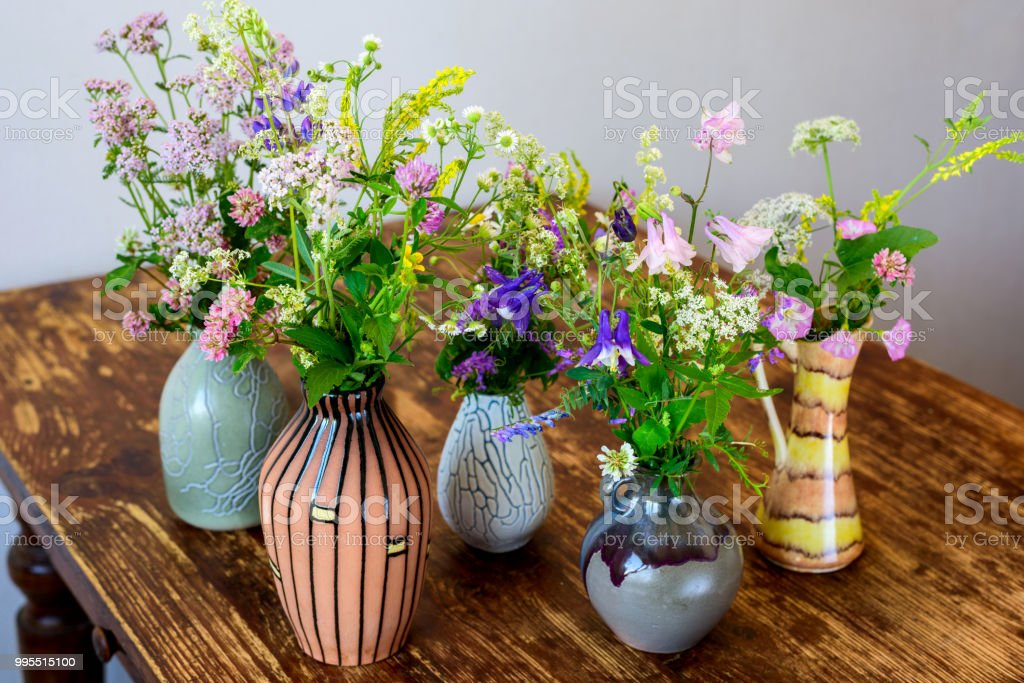 iStock & Bouquets Of Summer Wild Flowers In Vases On A Wooden Table Still Life In Rustic Style Stock Photo - Download Image Now