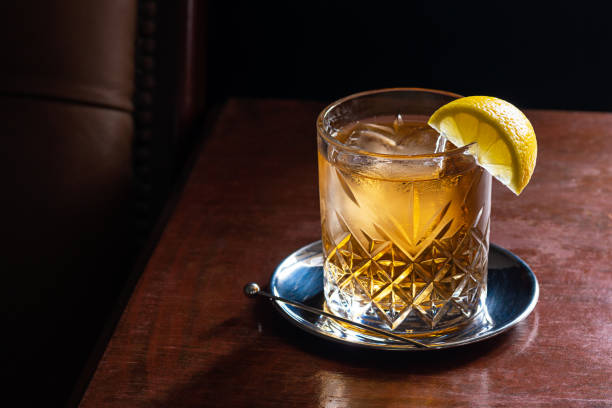 Bourbon, Scotch, or Whiskey and Soda Cocktail with Ice and Lemon in Dark Bar stock photo