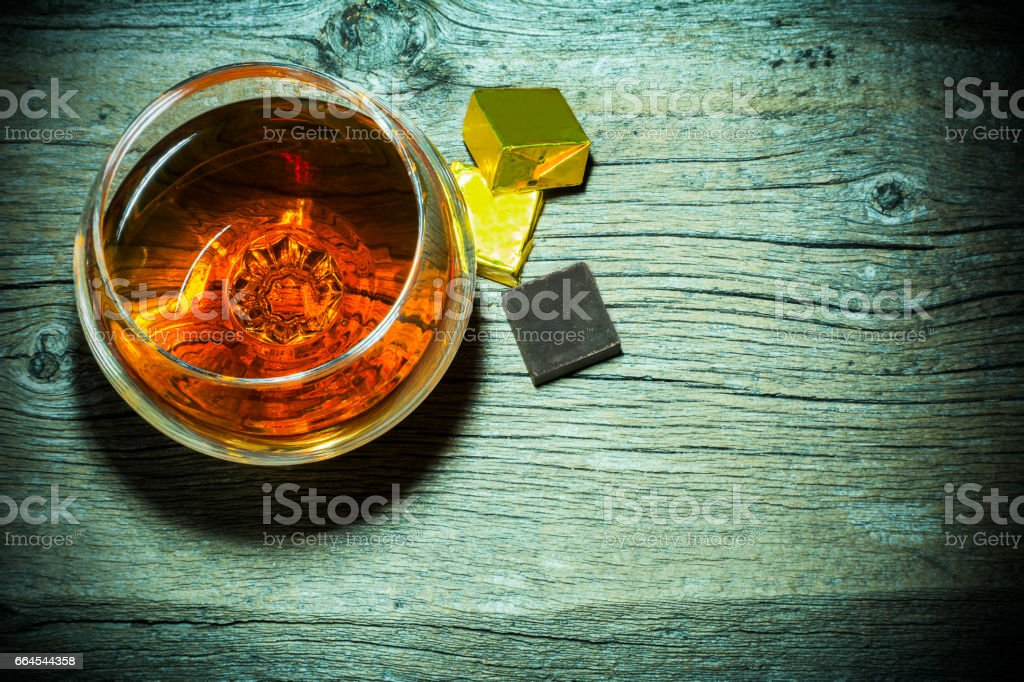 Bourbon snifter and chocolate on old wooden background top view stock photo