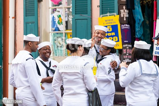 New Orleans, USA - April 23, 2018: Old town street in Louisiana city with happy people sailors group holding drinks talking on sidewalk during Navy Week