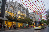 Melbourne, Australia - December 17, 2017: A tram goes past the Zara store at Bourke Street Mall, beneath numerous lines of Christmas lights.