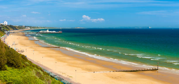 Bournemouth beach, pier, sea and sand Sunshine illuminates golden beaches and blue-green seas along the Dorset coast between Poole and Bournemouth groyne stock pictures, royalty-free photos & images