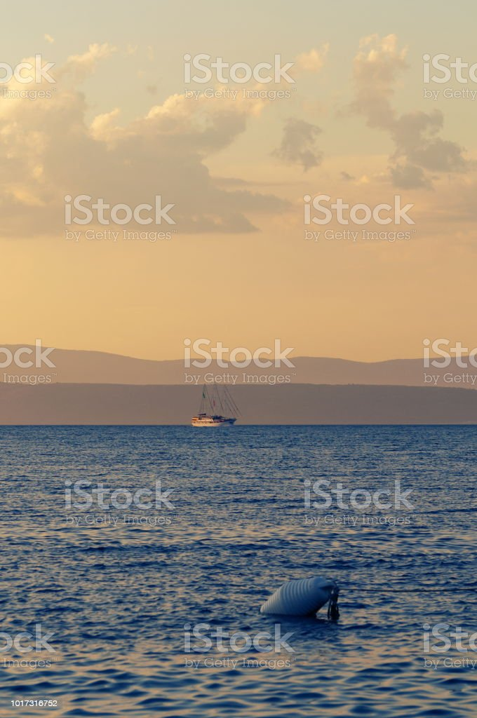 Bouy and boat in background lit with setting sun stock photo