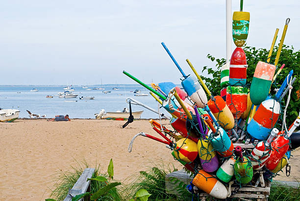 Bouys and Boats Colorful bouys and a view of the sea on a Provincetown beach in Cape Cod Massachusetts. provincetown stock pictures, royalty-free photos & images
