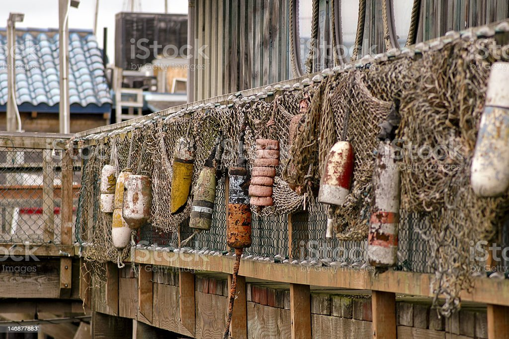 Bouys and netting on the side of a building stock photo