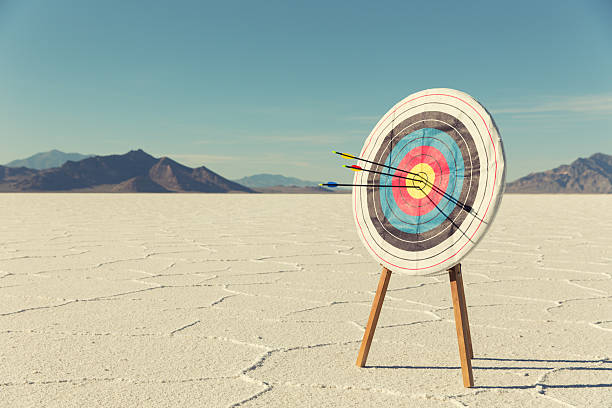 bow and arrow target with arrows - sports target stock photos and pictures