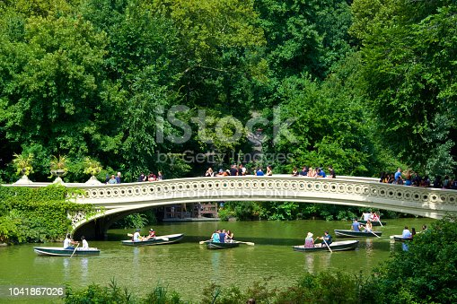 New York City, USA - August 25, 2018: People in rowboats are seen near the historic Bow Bridge on a summer's day in The Lake, Central Park, West Side of Manhattan.