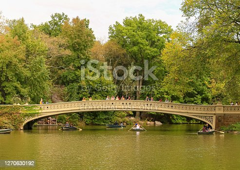 New York City, USA - October 7, 2019: The Bow Bridge in Central Park. Pepole walking across the bridge or looking in the lake. Rowing boats are under the bridge.