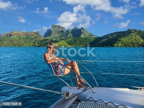 Happy woman in one on the bow seats on a catamaran. Bora Bora lagoon, French Polynesia. South Pacific Ocean.