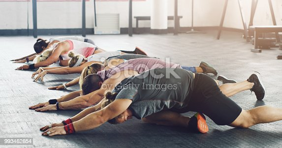 Shot of a group of young people working out together in a gym