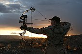 A male hunter draws back on his bow during an evening hunt