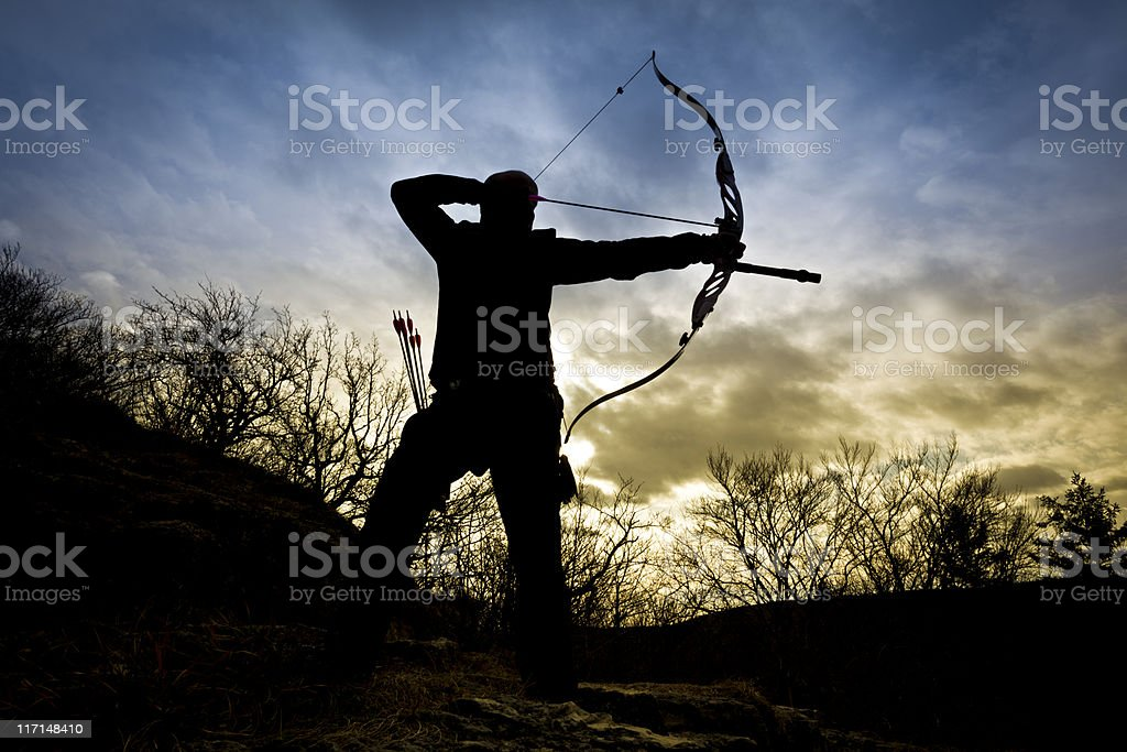 bow hunter silhouette in nature stock photo