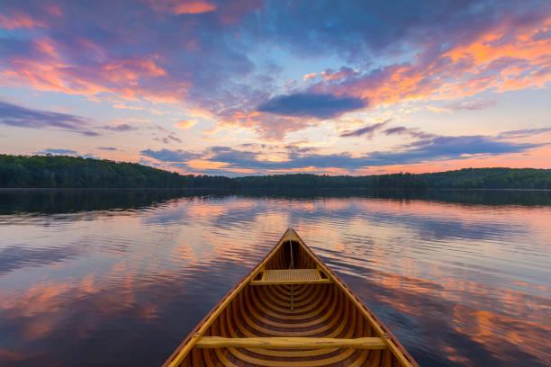 Bow of a cedar canoe on a lake at sunset - Ontario, Canada stock photo