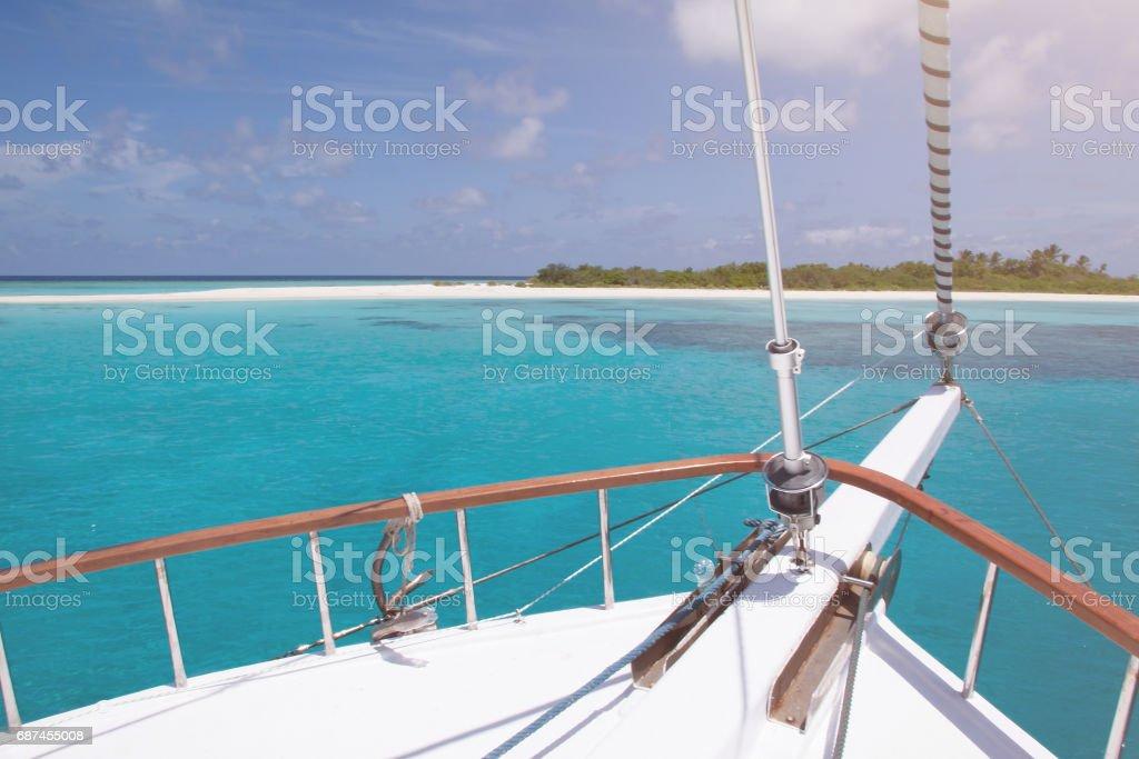 Bogen eines weißen Segelbootes Verankerung im türkisfarbenen Wasser mit tropischen Insel und blauer Himmel im Hintergrund – Foto