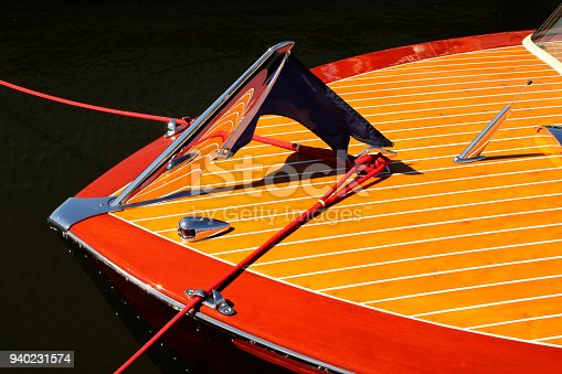 Bow of vintage wooden boat with crome reflecting wood stripes - red and yellow