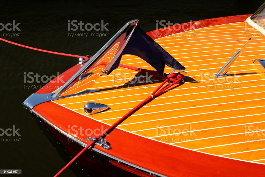 Bow of vintage wooden boat with crome reflecting wood stripes - red and yellow stock photo